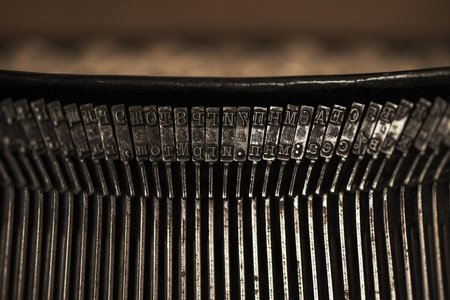 Antigua máquina de escribir negra con papel que vale sobre la mesa