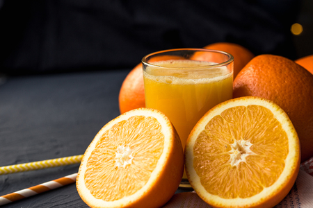 Fresh orange juice and fresh fruit oranges on a black background Banco de Imagens