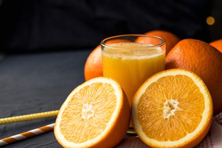 Succo d'arancia fresco e arance di frutta fresca su sfondo nero