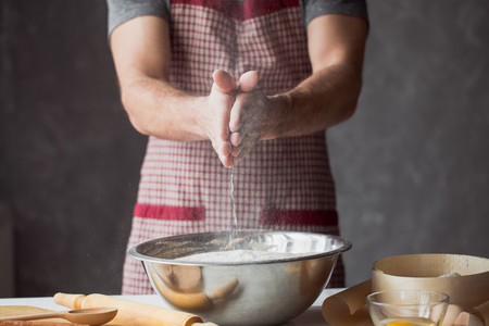 A handful of flour with egg on a rustic kitchen. Against the background of mens hands knead the dough Stock Photo
