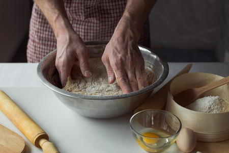 A handful of flour with egg on a rustic kitchen. Against the background of men's hands knead the dough