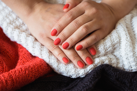 Closeup photo of a beautiful female hands with red nails Reklamní fotografie - 122025907