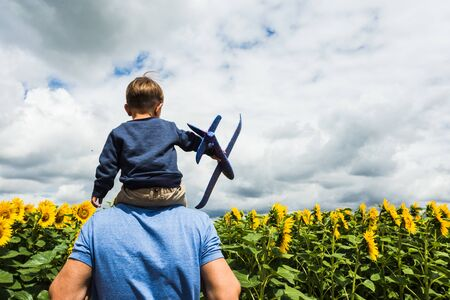 Father and son playing with a toy airplane near the sunflower field Reklamní fotografie