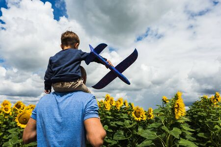 Father and son playing with a toy airplane near the sunflower field