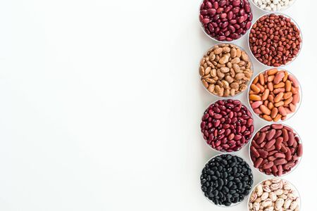 Different varieties of beans in plates are arranged in a row.