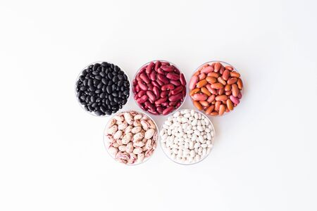 Different varieties of beans in round plates on white backround.