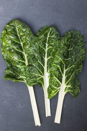 Fresh chard leaves on black background. Table top view fresh organic green food 版權商用圖片