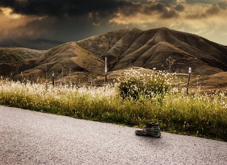 battered land: Landscape stormy one shoe worn on road   Stock Photo