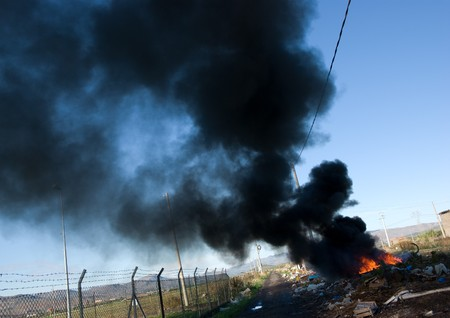 flames and black smoke of tires burning photo