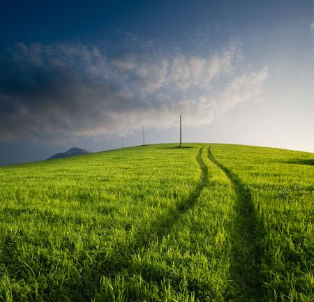 tracks cross cultivated hill at twilight Stock Photo