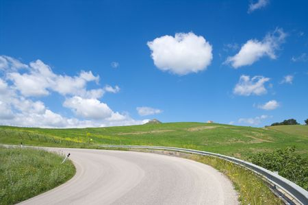 rural road crosses green hill on background blue sky and white clouds