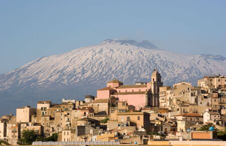 view of dwellings and belltower in the city of Centuripe in Sicily, on background the volcano Etna partly snowy