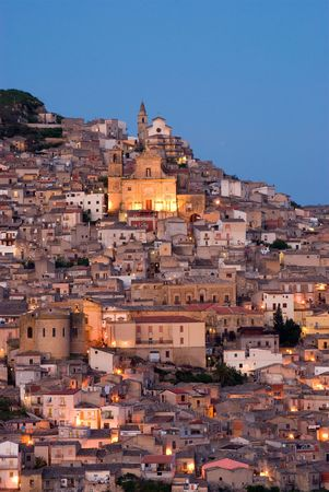 view crepuscular of dwellings and the church of Santa Margherita illuminated by street light in the city of Agira in Sicily photo