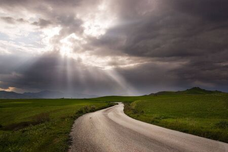 road crosses a prairie covered by clouds into rays of sun Banque d'images