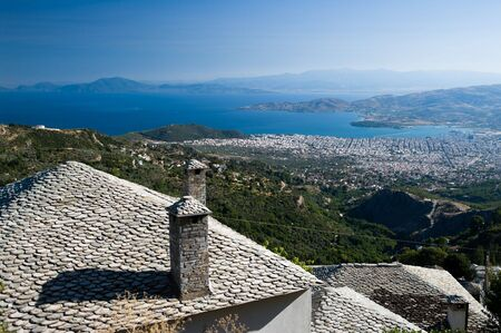 thessaly: foreground on traditional stone roof of Makrinitsa in background city of Volos on gulf of Pagassitikos, Greece Stock Photo