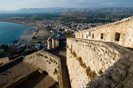 nafplio: The imposing walls of castle Palamidi, in background the bay and the village of Nafplion, Greece   Stock Photo