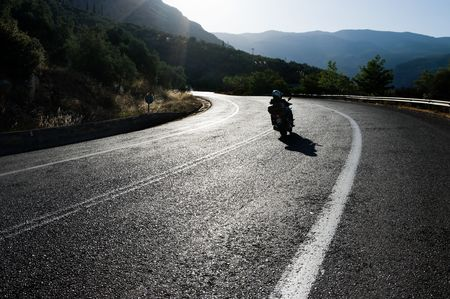 Motorbike bending in backlits on shiny asphalt of a Winding Road