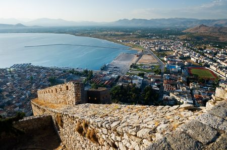 The imposing walls of castle Palamidi, in background the bay and the village of Nafplion, Greece   photo