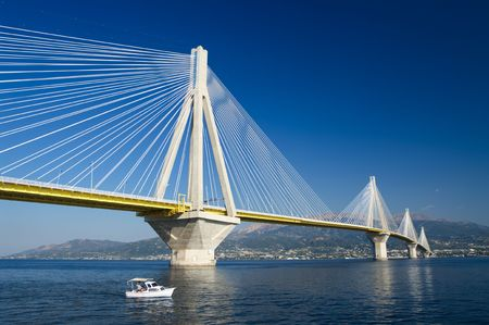 steel building: a small boat under the suspension bridge crossing Corinth Gulf strait, Greece.   Stock Photo