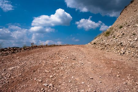 terreno: strada sterrata di terreno roccioso sulle nuvole nel cielo blu di sfondo Archivio Fotografico