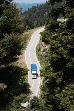 aerial view of truck crossing a forest of a mountain road  photo