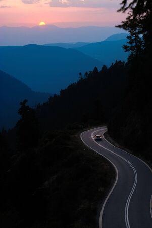 lineas verticales: Viajar en coche la carretera serpentea entre las monta�as al atardecer