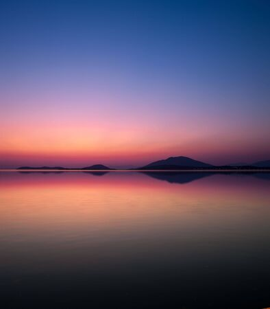 gloaming: reflection of coastline in the sea of the harbor of Igoumenitsa (Greece) at twilight