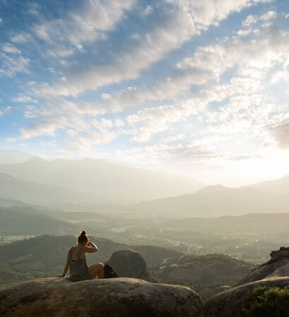 girl sitting on the rock of Meteora - Greece - and looking over the valley in a misty sunset photo