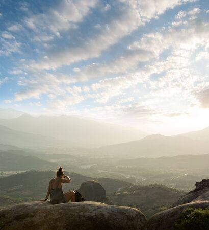 mujer mirando el horizonte: ni�a sentada en la piedra de Meteora - Grecia - y buscar sobre el valle, en una puesta de sol brumoso
