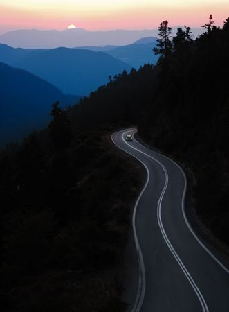 Auto slingerende weg te reizen tussen berg bij zons ondergang