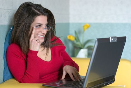 pretty girl is smiling and sitting on the yellow sofa with the laptop is looking over her glasses photo