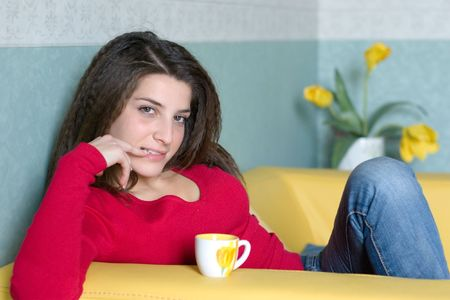 a pretty girl takes a break sipping a coffee on the yellow sofa  photo