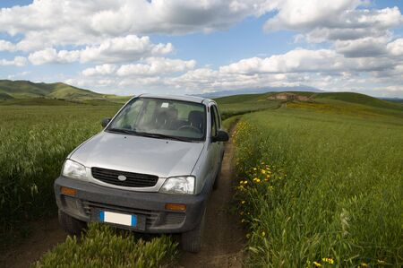 a vehicle off-road crosses a track in a oats field Stock Photo - 6190472