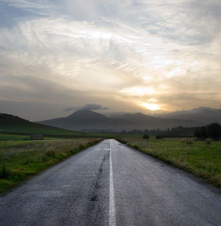dirt road: straight road crosses a desolate country road at the gloomy sunset Stock Photo
