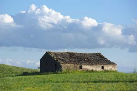 abandoned farmhouse abandoned farmhouse: abandoned farmhouse in a grassy field and cloudy sky