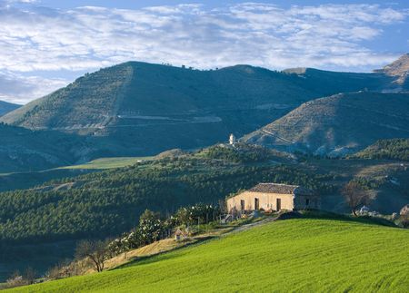 telephoto: old farmhouse on top of green field, on background hills and clouds