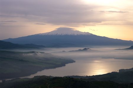 mist dawn on the water of the lake in background mount Etna photo
