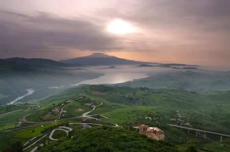 aerial view of countryside in dawn mist on the lake and on the background mount Etna. The picture was taken from Agira, Sicily Stock Photo - 6593641