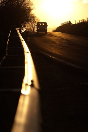 guardrail: vanish guardrail and front view of car with their lights on in the sunset
