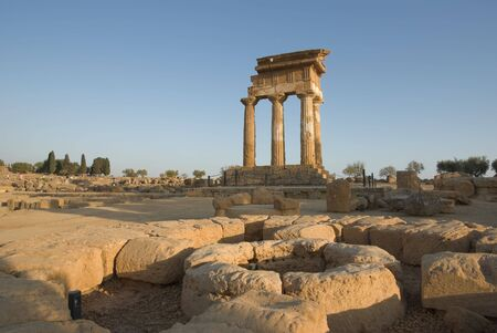 doric temple Of Castor and Pollux in the Valley Of Temples in Agrigento, on foreground circular altar stone photo