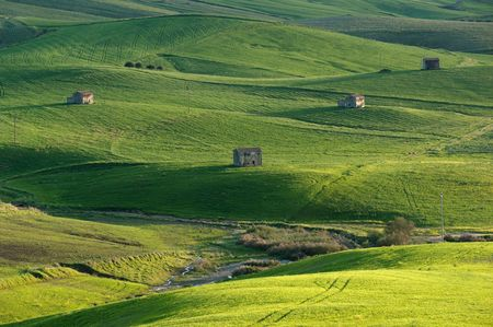 abandoned farmhouse on rolling hills to the last light of day photo
