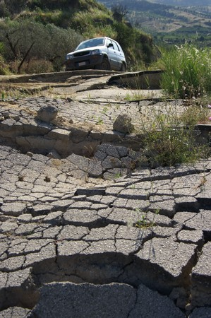 land slide: the landslip of a rural road on the blurred background an off-road car Stock Photo