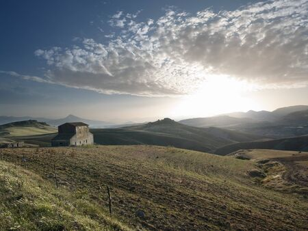 the sun is setting on the countryside with abandoned farmhouse in the sicilian hinterland Stock Photo - 6987463