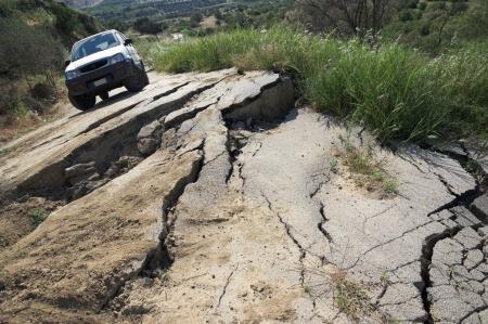 landslip: the landslide of a rural road on the background an off-road car