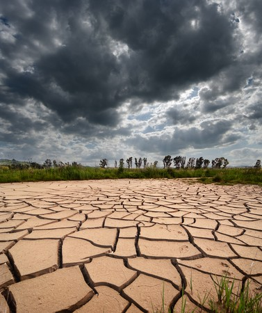 stormy clouds dark are gathering on dry and cracked land photo