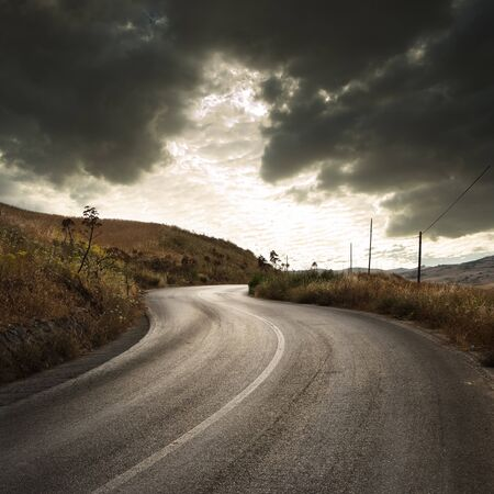 a winding road in countryside with gloomy cloudscape at the sunset  Stock Photo - 7252117