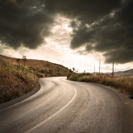 a winding road in countryside with gloomy cloudscape at the sunset    photo