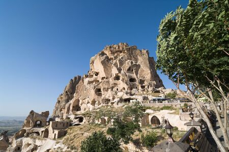 the Uchisar castle is a tall vulcanic rock outcrop riddled with tunnels and windows visible for miles around in Cappadocia, Turkey photo
