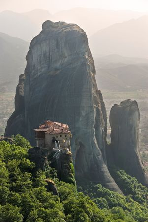 view of a monastery tower on top of a rock Meteora in haze evening  photo