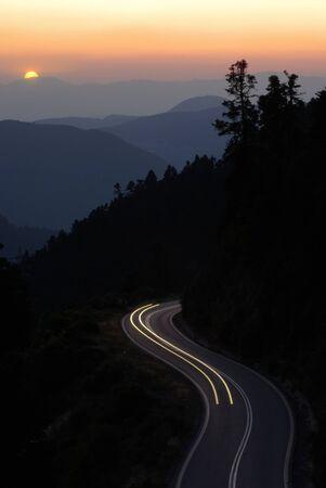 light trail: Sendero de luz en una monta�a de carretera sinuosa al atardecer
